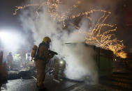 A firefighter extinguishes a container that was set alight during protests against a nation-wide curfew in Rotterdam, Netherlands, Monday, Jan. 25, 2021. The Netherlands Saturday entered its toughest phase of anti-coronavirus restrictions to date, imposing a nationwide night-time curfew from 9 p.m. until 4:30 a.m. in a bid to control the COVID-19 infection rate. (AP Photo/Peter Dejong)