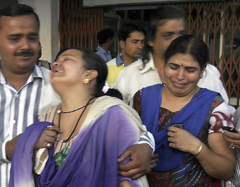 In this Saturday, May 25, 2013 photo, unidentified relatives of an injured of a rebel attack cry outside a government hospital in Raipur, India. About 200 suspected Maoist rebels set off a land mine and opened fire on a convoy of cars carrying local leaders and supporters of India's ruling Congress party in the country's east, killing at least 28 people and wounding 24 others, police said. (AP Photo)