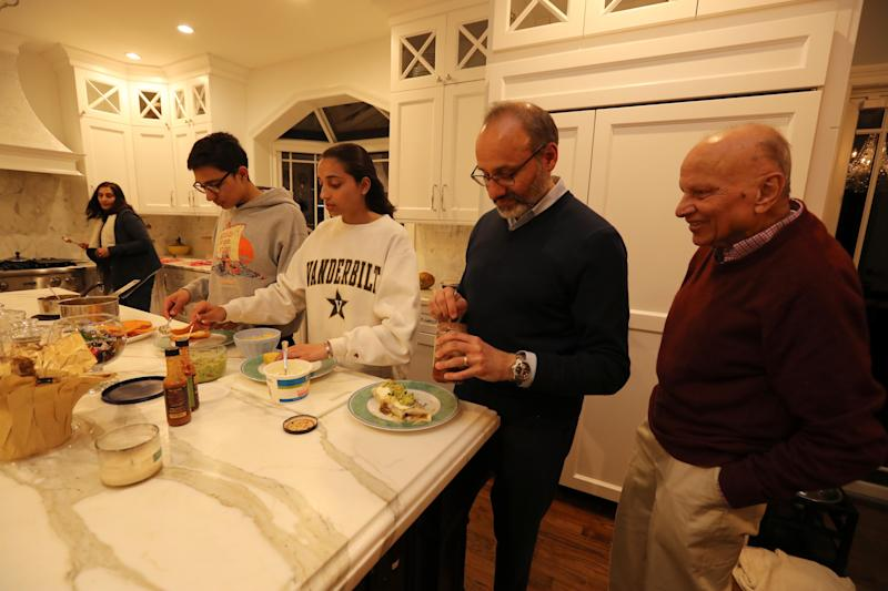 From left, Bella Sheth, her son Kiran, 16, daughter Serena, 18, her husband Haresh, and Rashmi Sheth, Hareth's father, put together a Mexican dinner at their home in Chappaqua April 1, 2019. The family spoke about the fact that that there are two Democratic candidates for President with Indian and Hindu connections.