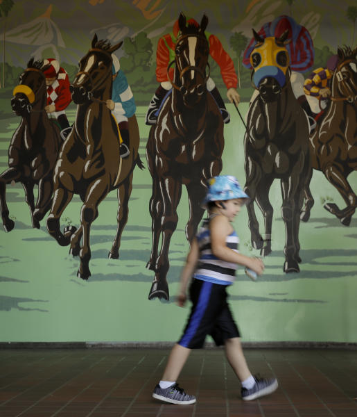 A youngster makes his way the the stands during the last day of the winter/spring meet at the Santa Anita horse racing track Sunday, June 23, 2019, in Santa Anita, Calif. (AP Photo/Chris Carlson)
