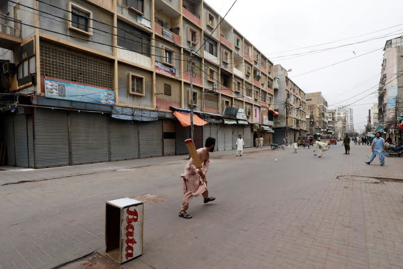 Shopkeepers play cricket along closed market amid the COVID-19 outbreak in Karachi