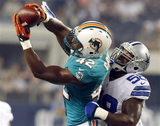 Miami Dolphins running back Charles Clay (42) makes a reception as Dallas Cowboys linebacker Orie Lemon (58) defends during the first half of a preseason NFL football game, Wednesday, Aug. 29, 2012, in Arlington, Texas. (AP Photo/Sharon Ellman)
