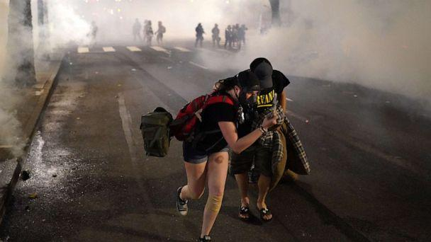 PHOTO: Two protesters flee through tear gas after federal officers dispersed a crowd of about a thousand at the Mark O. Hatfield U.S. Courthouse on July 21, 2020 in Portland, Ore. (Nathan Howard/Getty Images)
