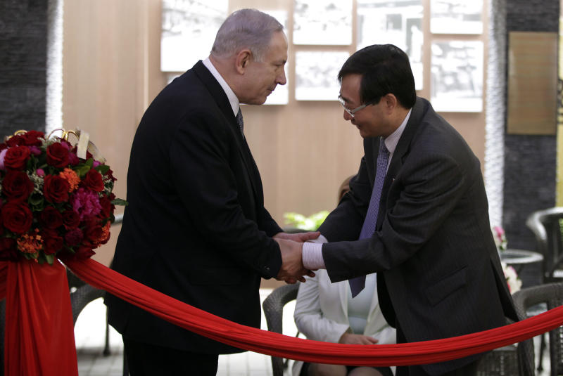 Israeli Prime Minister Benjamin Netanyahu, left, and a local Chinese official, right, shake hands at the Shanghai Jewish Refugees Museum in Shanghai, China, Tuesday, May 7, 2013. China is hosting both the Palestinian and Israeli leaders this week in a sign of its desire for a larger role in the Middle East. (AP Photo/Eugene Hoshiko)