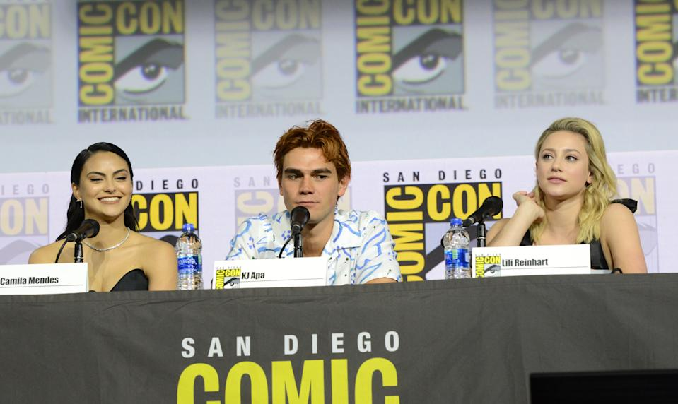 """SAN DIEGO, CALIFORNIA - JULY 21: (L-R) Camila Mendes, KJ Apa and Lili Reinhart speak at the """"Riverdale"""" Special Video Presentation and Q&A during 2019 Comic-Con International at San Diego Convention Center on July 21, 2019 in San Diego, California. (Photo by Albert L. Ortega/Getty Images)"""