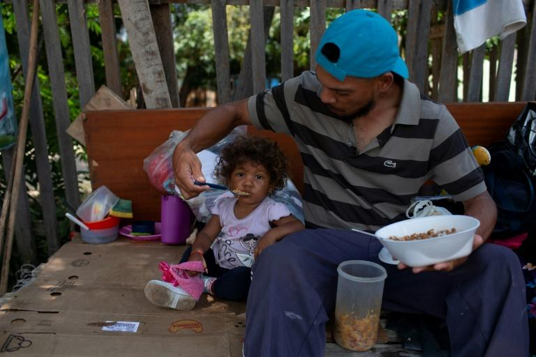 A Venezuelan man and his daughter eat a meal on the roadside in Boa Vista, Roraima state, a Brazilian town where 25,000 Venezuelans have gathered, part of an exodus from the imploding economy back home