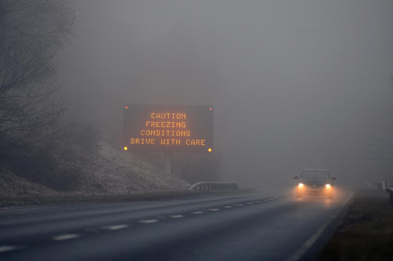 LOCH LOMOND, SCOTLAND - DECEMBER 12:  A car drives on the A82 past a road traffic sign on December 12, 2012 in Loch Lomond, Scotland. Forecasters have warned that the UK could experience the coldest day of the year so far today, with temperatures dropping as low as -14C, bringing widespread ice, harsh frosts and freezing fog. Travel disruption is expected with warnings for heavy snow in some parts of the country.  (Photo by Jeff J Mitchell/Getty Images)