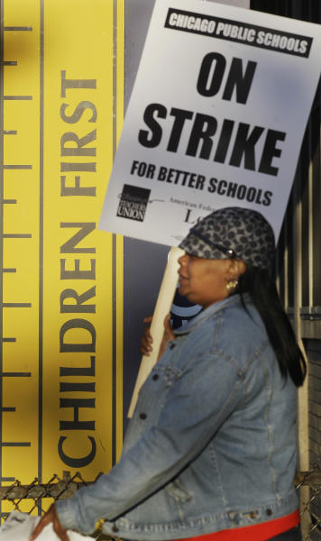 Chicago teacher Alma Hill walks a picket line outside Benjamin Banneker Elementary School in Chicago, Monday, Sept. 10, 2012, after the teachers went on strike for the first time in 25 years. Union and district officials failed to reach a contract agreement despite intense weekend negotiations. (AP Photo/M. Spencer Green)