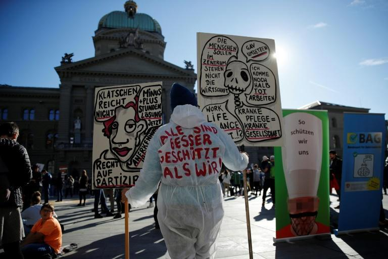 "A healthcare worker wears a PPE suit reading in German ""All are better protected than we are!"" outside the Swiss House of Parliament during a demonstration in Bern"