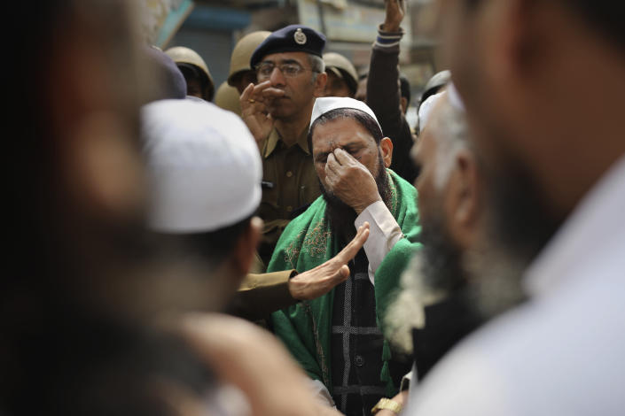 FILE - In this Friday, Feb. 28, 2020, file photo, a man gestures as a senior Delhi police officer speaks to a group of Muslims ahead of Friday prayers near a heavily-policed fire-bombed mosque in New Delhi, India. Many of the Muslim victims of last year's bloody violence say they have run repeatedly into a refusal by police to investigate complaints against Hindu rioters. Some hope the courts will still come to their help. But others now believe the justice system under Prime Minister Narendra Modi's Hindu-nationalist government has become stacked against them. (AP Photo/Altaf Qadri, File)