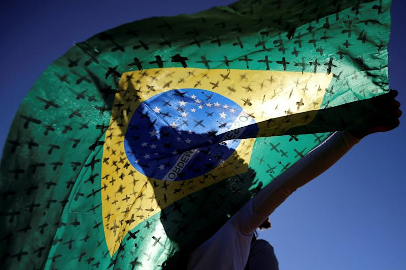 An activist holds a Brazilian flag painted with crosses symbolising the ones who died from the coronavirus disease (COVID-19) in front of the National Congress during a protest against Brazil's President Jair Bolsonaro in Brasilia, Brazil July 14, 2020. REUTERS/Adriano Machado TPX IMAGES OF THE DAY