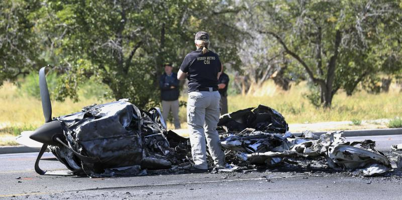 A investigator looks at the wreckage of a small plane that struck a car when it crashed into a neighborhood in Roy, Utah on Sept. 12, 2017.