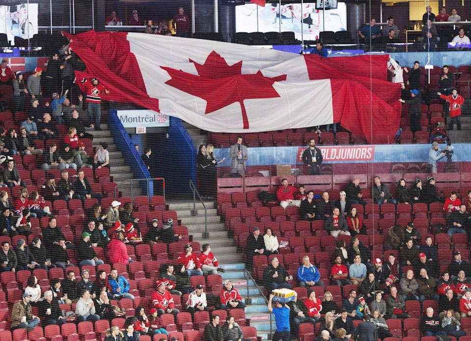 Empty seats are seen as fans pass around a giant Canadian flag before the quarter-final IIHF World Junior Championships hockey game between Czech Republic and Canada Monday, January 2, 2017 in Montreal. THE CANADIAN PRESS/Ryan Remiorz