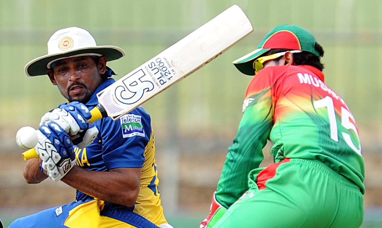 Sri Lankan cricketer Tillakaratne Dilshan (L) plays a shot as Bangladesh cricket captain Mushfiqur Rahim (R) looks on during the third and final one-day international (ODI) match between Sri Lanka and Bangladesh at The  Pallekele International Cricket Stadium in Pallekele on March 28, 2013. AFP PHOTO/ Ishara S. KODIKARA        (Photo credit should read Ishara S.KODIKARA/AFP/Getty Images)
