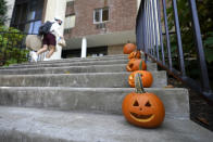 A man wears a face mask to protect against COVID-19 while walking near Jack-o'-lanterns line up on steps at Belmont University, the site of the final presidential debate between Republican President Donald Trump and Democratic candidate former Vice President Joe Biden, Tuesday, Oct. 20, 2020, in Nashville, Tenn. The debate is scheduled for Thursday, Oct. 22. (AP Photo/Julio Cortez)