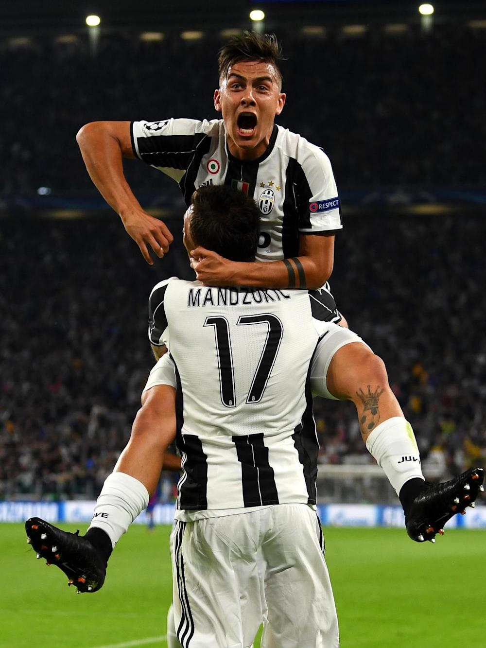 The Argentine celebrates with Mario Mandzukic after scoring his second against Barca (Getty)