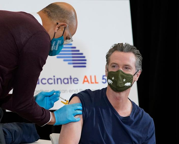 Dr. Mark Ghaly, California's Health and Human Services secretary, inoculates California Gov. Gavin Newsom, at the Baldwin Hills Crenshaw Plaza in Los Angeles Thursday, April 1, 2021. Newsom was vaccinated with the new one-dose COVID-19 vaccine by Johnson & Johnson.