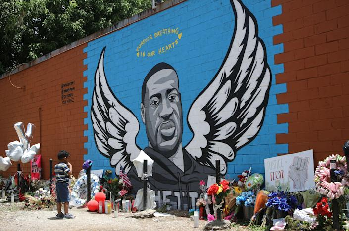 <p>A child views a mural dedicated to George Floyd, across the street from the Cuney Homes housing project in Houston's Third Ward, where Floyd grew up and later mentored young men, on June 10, 2020 in Houston, Texas. </p> ((Photo by Mario Tama/Getty Images))