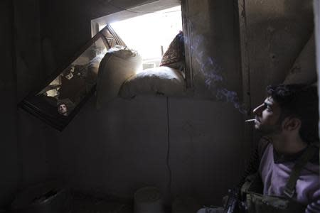 A Free Syrian Army fighter smokes while monitoring an area through a mirror inside a room in Deir al-Zor September 28, 2013. REUTERS/Khalil Ashawi
