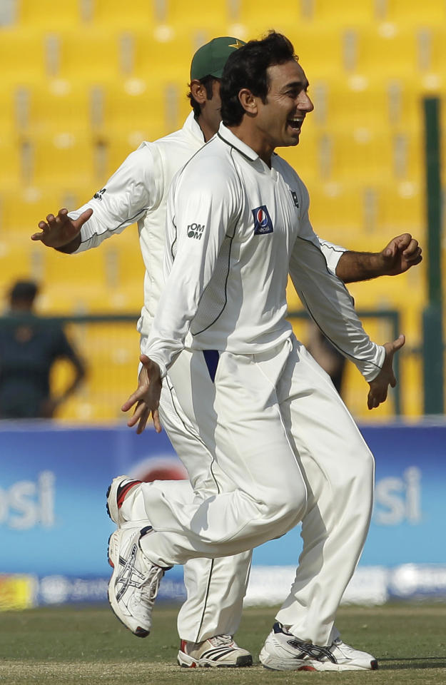 Pakistan's Saeed Ajmal celebrates with his teammates taking the wicket of England's Ian Bell during the fourth day of the second cricket Test match of a three match series between England and Pakistan at Zayed Cricket Stadium in Abu Dhabi, United Arab Emirates, Saturday, Jan. 28, 2012. (AP Photo/Hassan Ammar)