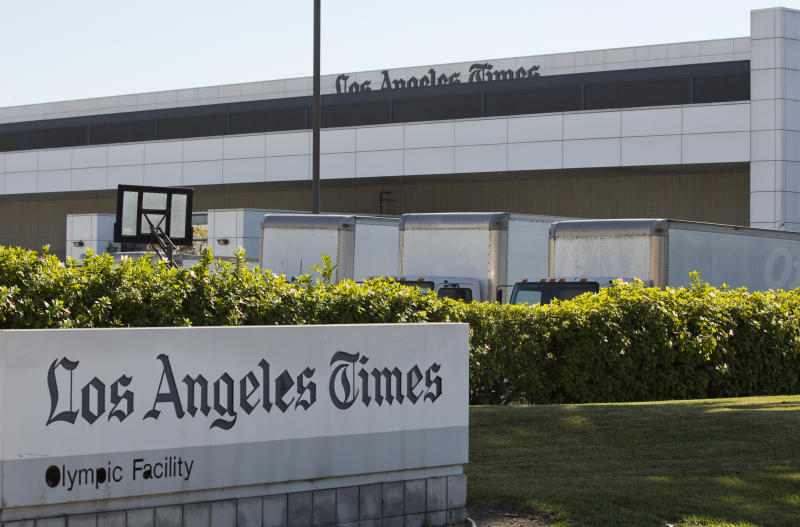 Delivery trucks are parked outside the Los Angeles Times Olympic Facility in Los Angeles, Sunday, Dec. 30, 2018. A computer virus hit the newspaper printing plant in Los Angeles, and at Tribune Publishing newspapers across the country. (AP Photo/Damian Dovarganes)
