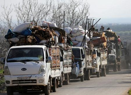 People ride on trucks with their belongings in north-east Afrin