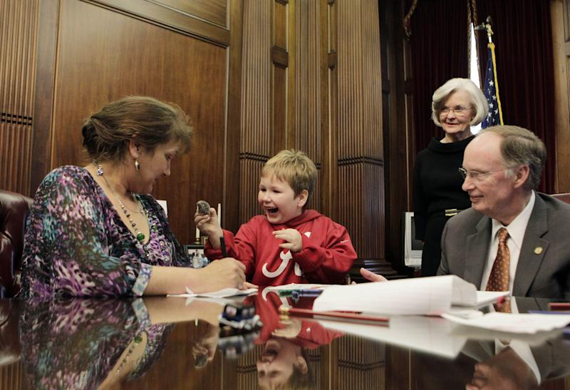 In this photo provided by the Governor's office, from right to left, Alabama Gov. Robert Bentley and First Lady Dianne Bentley watch as Ethan Gilman shows his mother, Jennifer Kirkland, a toy mouse Bentley gave him to play with on a visit to the Governor's Office in Montgomery, Ala. on Wednesday, Feb. 13, 2012. Ethan was held hostage in an underground bunker in a near week-long standoff in Midland City, Ala. (AP Photo/Alabama Governor's Office, Jamie Martin)