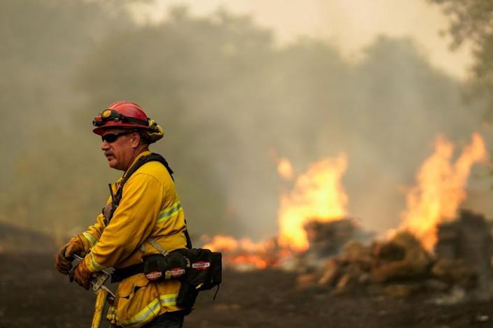 """A firefighter battles the Hennessy fire in Vacaville, Calif., on Wednesday. <span class=""""copyright"""">(Kent Nishimura / Los Angeles Times)</span>"""