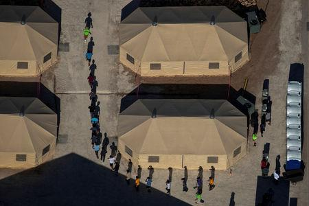 FILE PHOTO: Migrant children are led by staff in single file between tents at a detention facility next to the Mexican border in Tornillo