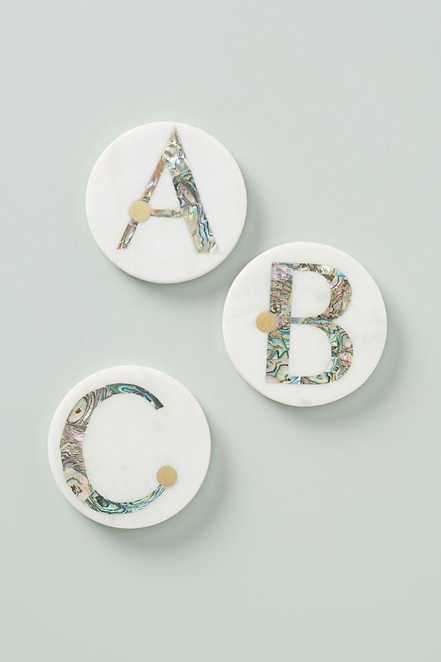 """<p><strong>Anthropologie</strong></p><p>anthropologie.com</p><p><strong>$11.20</strong></p><p><a href=""""https://go.redirectingat.com?id=74968X1596630&url=https%3A%2F%2Fwww.anthropologie.com%2Fshop%2Fgwen-monogram-coaster&sref=https%3A%2F%2Fwww.womansday.com%2Flife%2Fg26963417%2Fpersonalized-mothers-day-gifts%2F"""" rel=""""nofollow noopener"""" target=""""_blank"""" data-ylk=""""slk:Shop Now"""" class=""""link rapid-noclick-resp"""">Shop Now</a></p><p>Now your mom will have somewhere to put her <a href=""""https://www.womansday.com/food-recipes/food-drinks/g2889/easter-cocktails/"""" rel=""""nofollow noopener"""" target=""""_blank"""" data-ylk=""""slk:spring cocktails"""" class=""""link rapid-noclick-resp"""">spring cocktails</a>! These coasters are made from marble with an inlay of brass and abalone shell. They'll be such a chic addition to her home.</p>"""