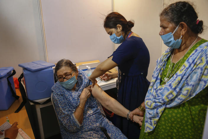 An elderly woman, left, holds the arm of her domestic helper as she receives Covishield vaccine against the coronavirus at a vaccination center in Mumbai, India, Tuesday, June 22, 2021. (AP Photo/Rafiq Maqbool)
