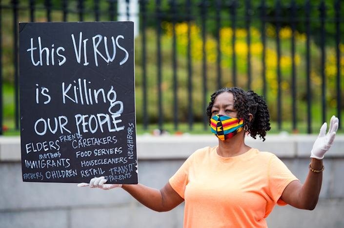 Alice Gaskins holds a sign in front of the Massachusetts State House during a funeral procession for essential workers that have been sick with or died from COVID-19 on May 25, 2020.