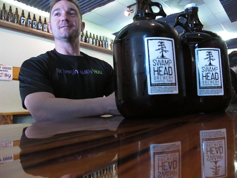 In this Friday, March 29, 2013 photo, patron Adam Rudell, of St. Petersburg, Fla., sits with two gallon-sized jugs of beer, known among beer enthusiasts as growlers, at the Swamp Head Brewery in Gainesville, Fla. Quart and gallon growlers are legal in Florida but half-gallon growlers are illegal. (AP Photo/Brendan Farrington)
