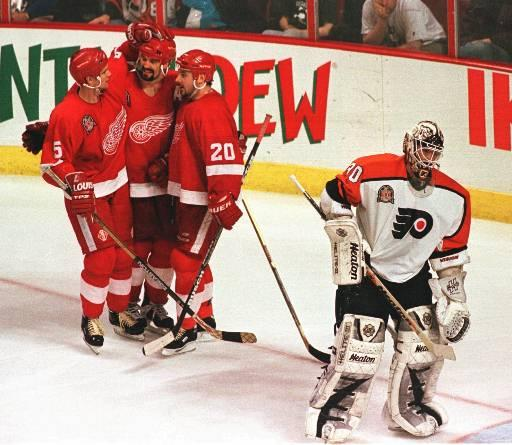 Detroit Red Wings Brendan Shanahan, center, is congratulated by teammates Nicklas Lidstrom (5) and Martin Lapointe (20) as Philadelphia Flyers Garth Snow skates away in the third period of Game 2 of the Stanley Cup finals, Tuesday, June 3, 1997, in Philadelphia. The Red Wings defeated the Flyers 4-2 to take a 2-0 lead in the series. (AP Photo/Rusty Kennedy)