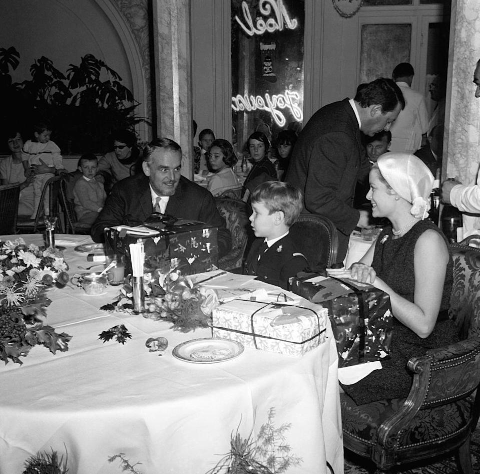 <p>Grace Kelly, Prince Rainier (left), and a young Prince Albert receive Christmas presents while attending a holiday party in Monaco. </p>