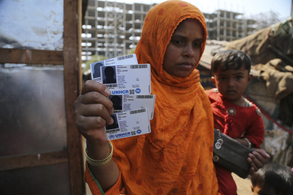 FILE - In this March 9, 2021 file photo, Rahima Kato, a Rohingya woman displays identity cards of her family members issued by United Nations High Commissioner for Refugees (UNHCR) at their makeshift camp on the outskirts of Jammu, India. Four Indian states bordering Myanmar have stepped up measures to prevent refugees from entering India through a porous border following last month's military coup in the Southeast Asian country, a government official said Saturday. (AP Photo/Channi Anand)