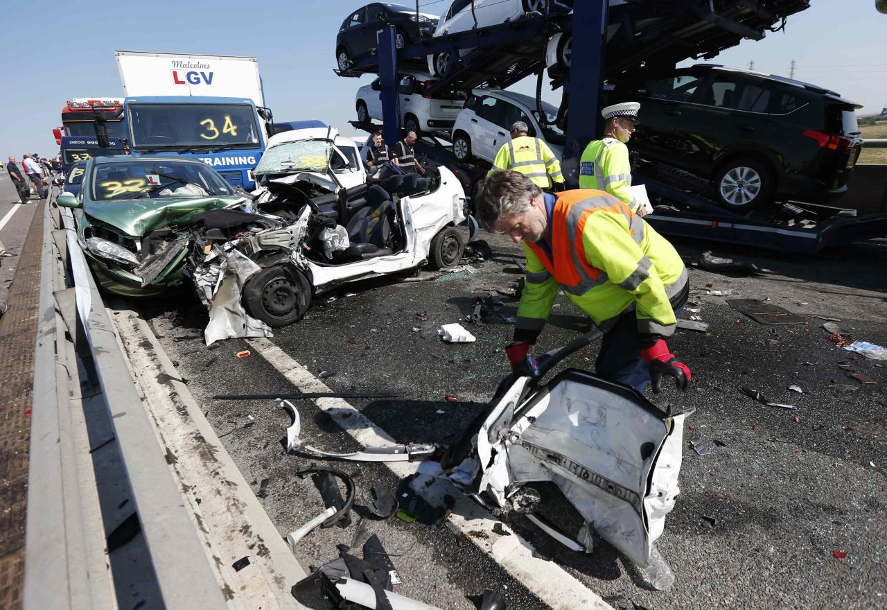 A rescue worker works amongst the wreckage of some of the 100 vehicles involved in multiple collisions, which took place in dense fog during the morning rush hour, on the Sheppey Bridge in Kent, east of London, September 5, 2013. Eight people were seriously injured and dozens hurt in the multiple crashes. REUTERS/Suzanne Plunkett (BRITAIN - Tags: TRANSPORT DISASTER)