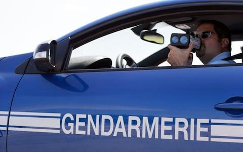 A French gendarme uses a radar gun to check the speed of cars driving on the highway A6-A31 on July 6, 2013 in Beaune, eastern France - Credit: AFP