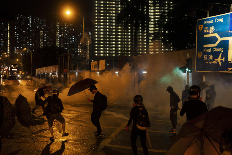 "In this Oct. 6, 2019, photo, protestors face police tear gas in Hong Kong. Shouting ""Wearing mask is not a crime,"" tens of thousands of protesters braved the rain Sunday to march in central Hong Kong as a court rejected a second legal attempt to block a mask ban aimed at quashing violence during four months of pro-democracy rallies. (AP Photo/Felipe Dana, File)"