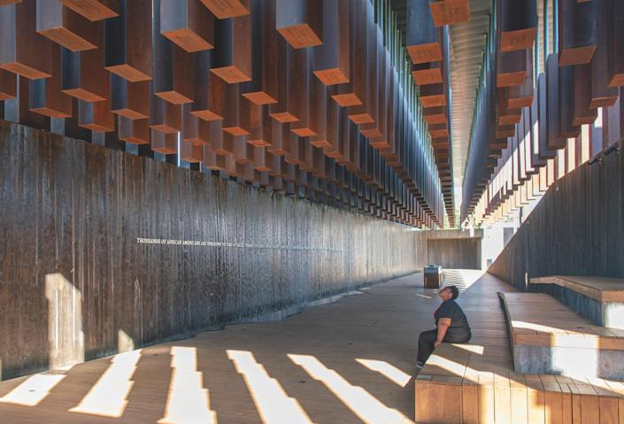 Designed by MASS Design Group, the National Memorial for Peace and Justice pays tribute to the 4,400 Black Americans murdered in lynchings from 1877 to 1950. Six-foot-tall CorTen steel slabs hang from the ceiling of the pavilion, each representing one of the 816 U.S. counties where a lynching took place. Established by human rights lawyer and Equal Justice Initiative executive director Bryan Stevenson, the memorial was designed to change over time, as the respective counties claim their corresponding slabs that surround the pavilion and place them in their communities following an acknowledgment and reconciliation process.