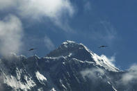 FILE - In this May 27, 2019, file photo, birds fly as Mount Everest is seen from Namche Bajar, Solukhumbu district, Nepal. A year after Mount Everest was closed to climbers as the pandemic swept across the globe, hundreds are making the final push to the summit with only a few more days left in the season, saying they are undeterred by a coronavirus outbreak in base camp. (AP Photo/Niranjan Shrestha, File)