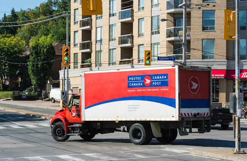 TORONTO, ONTARIO, CANADA - 2015/08/13: Red and white color Canada Post delivery truck passing through a traffic junction. Canada Post or Postes Canada, is the crown corporation which functions as the country's primary postal operator. It was earlier known as Royal Mail Canada. (Photo by Roberto Machado Noa/LightRocket via Getty Images)