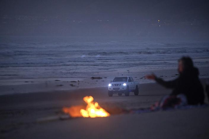 A beach bonfire with a truck in the background