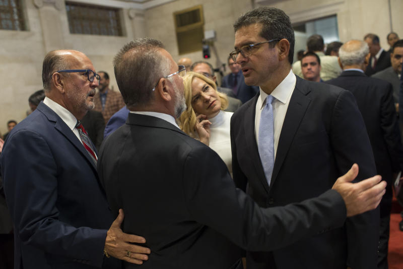 Proposed Secretary of State Pedro Pierluisi, right, is greeted by lawmakers Luis Ortiz and Jose Aponte during a break in his confirmation hearing at the House of Representatives, in San Juan, Puerto Rico, Friday, August 2, 2019. As Gov. Ricardo Rossello is expected to leave office in a few hours, the Puerto Rican House of Representatives is expected to vote on Pierluisi's confirmation Friday afternoon. If he is rejected, Justice Secretary Wanda Vazquez automatically becomes governor as the next in the order of succession, even though she has said she would unwillingly accept the job. (AP Photo/Dennis M. Rivera Pichardo)