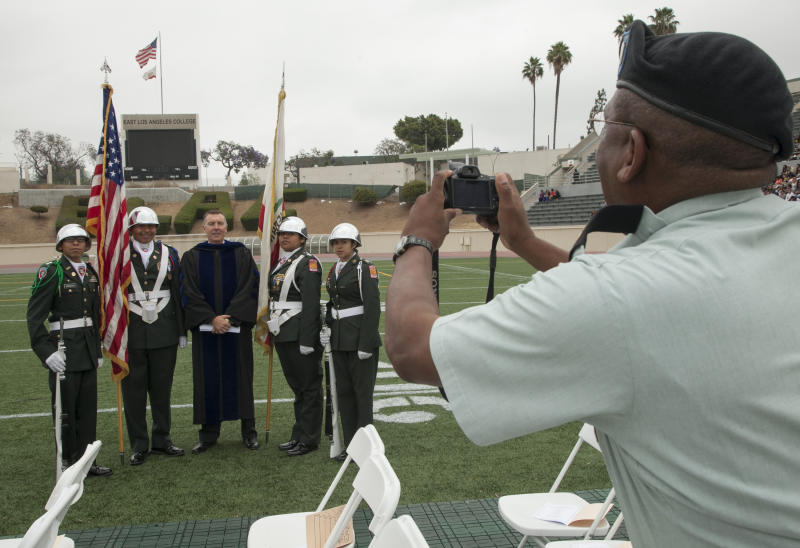 In this photo taken Thursday, June 14, 2012, Los Angeles Unified School District LAUSD Superintendent John Deasy poses with an honor guard during a gradution ceremony. Developing school leadership is a cornerstone of Deasy's strategy to reform Los Angeles Unified School District and sorting through principals underscores his philosophy that nothing in the sprawling district is too minute to warrant his attention. (AP Photo/Damian Dovarganes)
