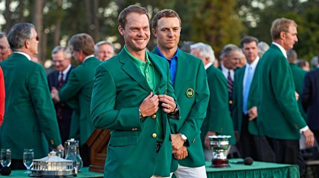 Jordan Spieth looks on as Danny Willett poses for photographs in his green jacket.