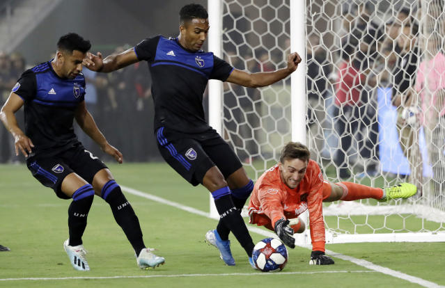 Los Angeles FC goalkeeper Tyler Miller, right, lunges for the ball as San Jose Earthquakes forward Danny Hoesen, center, closes in during the first half of an MLS soccer match Wednesday, Aug. 21, 2019, in Los Angeles. (AP Photo/Marcio Jose Sanchez)