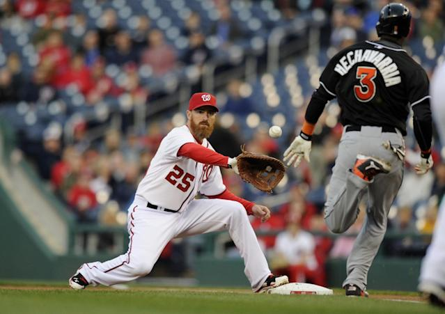 Miami Marlins' Adeiny Hechavarria (3) is out at first against Washington Nationals first baseman Adam LaRoche (25) during the first inning of a baseball game, Tuesday, April 8, 2014, in Washington. (AP Photo/Nick Wass)