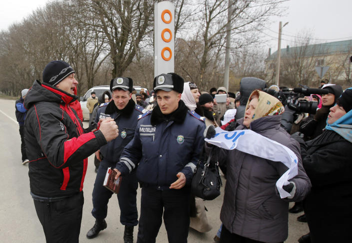 """A pro-Russian supporter, left, argues with Crimean Tatars demonstrating during a pro-Ukraine rally in Simferopol, Crimea, Ukraine, Monday, March 10, 2014. Russian President Vladimir Putin on Sunday defended the separatist drive in the disputed Crimean Peninsula as in keeping with international law, but Ukraine's prime minister vowed not to relinquish """"a single centimeter"""" of his country's territory. The local parliament in Crimea has scheduled a referendum for next Sunday. (AP Photo/Darko Vojinovic)"""