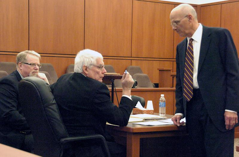 Defense attorney Al Avignone, right, speaks with Richland County Attorney Mike Weber, center, at the competency hearing for murder suspect Michael Keith Spell on Tuesday, March 25, 2014 in Sidney, Mont. Deputy County Attorney T.R. Halvorson, left, looks on. A state psychiatrist testified that Spell is fit for trial. (AP Photo/Matthew Brown)